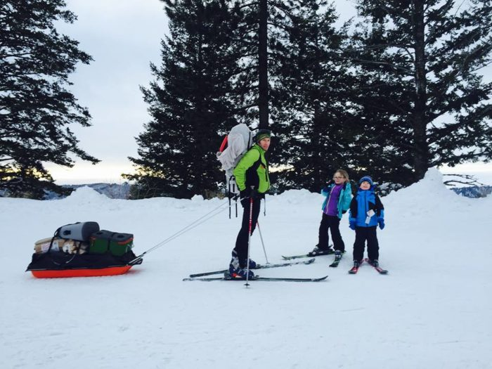 Dad with two young kids on nordic skis, dad ready to pull the sled laden with gear for an overnight stay.