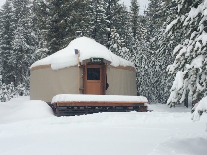 Snow-covered yurt surrounded by snow-covered trees.