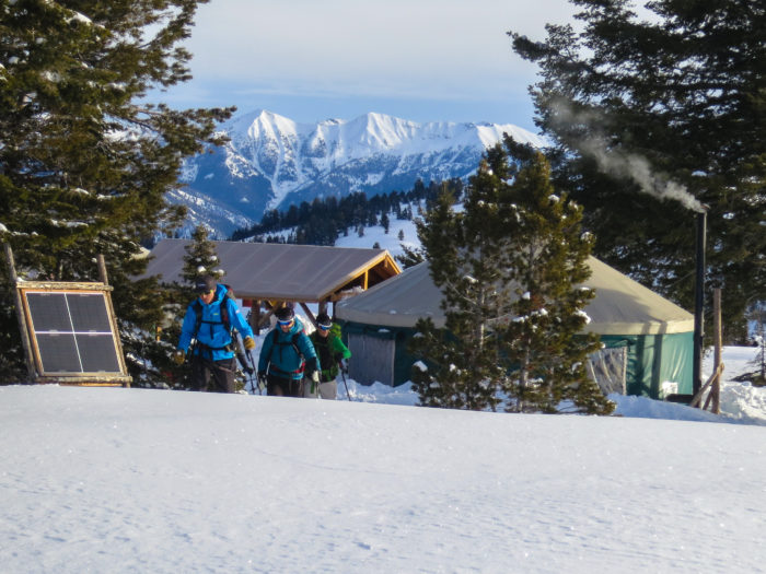 Three men leaving a yurt with a dramatic snow-capped mountain view in the background.