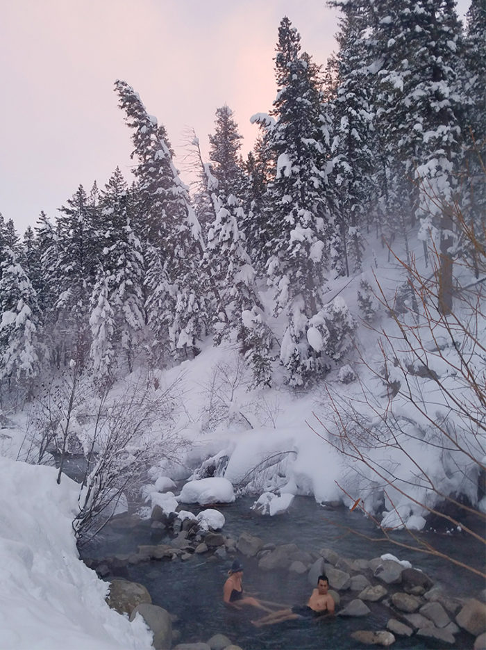 people sitting in hot pool along river in the snow