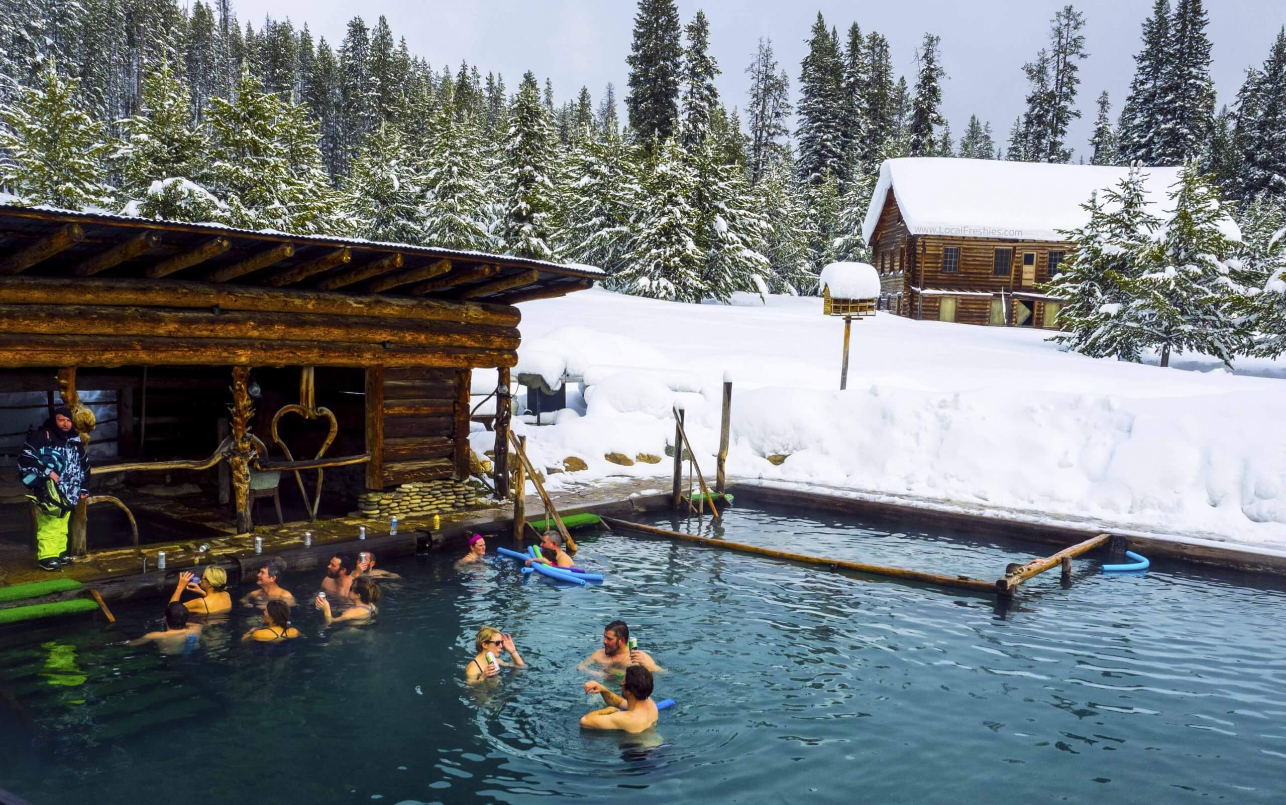 People sitting a hot pool surrounded by snow.