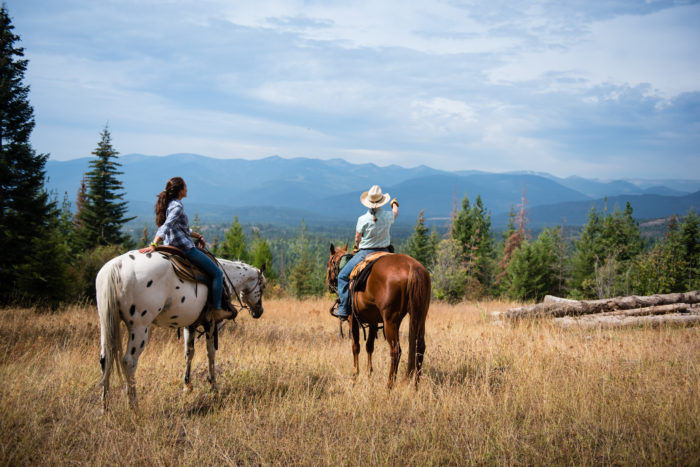 two women on horses looking over mountain valley