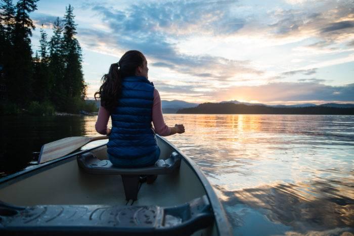 woman paddles canoe on lake at sunset