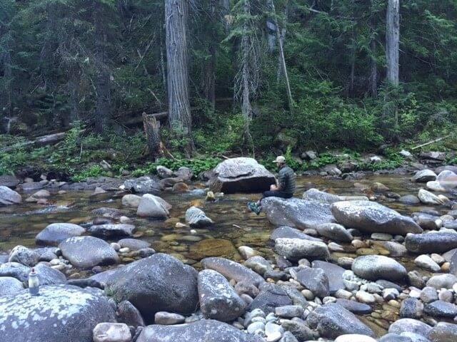 man sitting alongside mountain creek