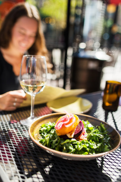 salad and glass of wine on outdoor patio
