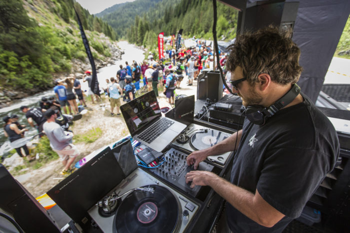 dj with a crowd along the river