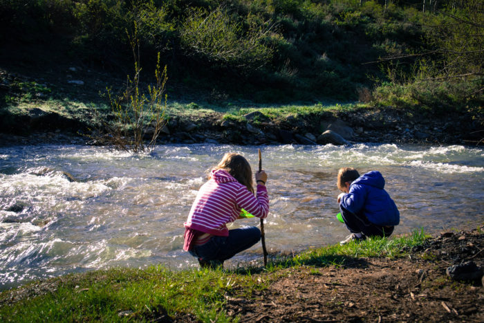 kids panning for gold in a creek