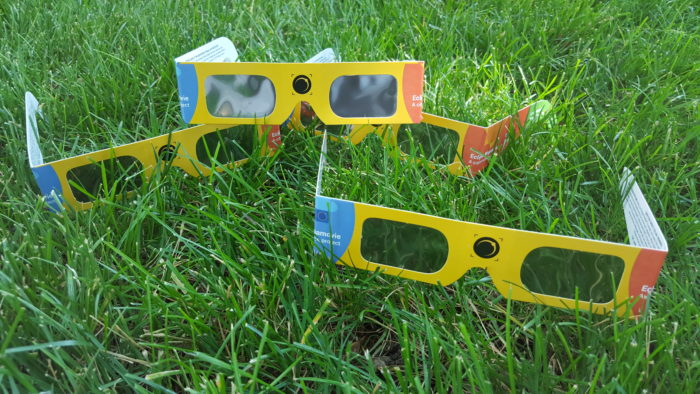 Four eclipse glasses sitting in grass.