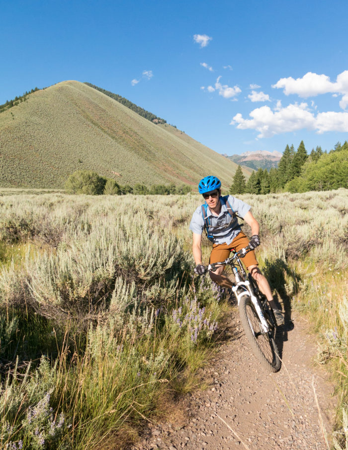 MOUNTAIN BIKER RIDING THROUGH SAGE BRUSH