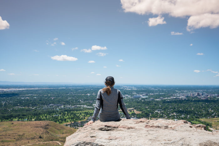 WOMAN SITTING ON ROCK LOOKING OVER VALLEY
