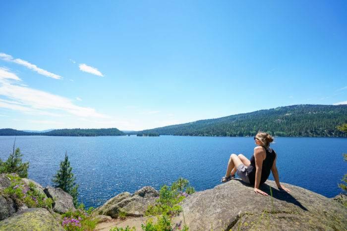 woman sitting on a rock near a lake