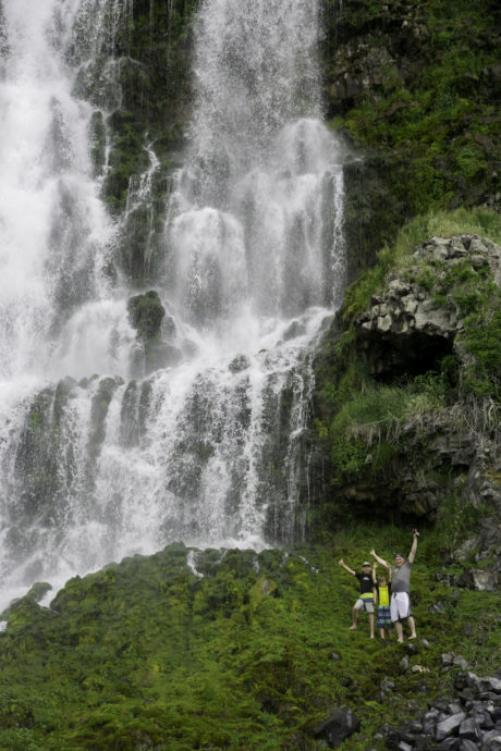 people standing next to a waterfall
