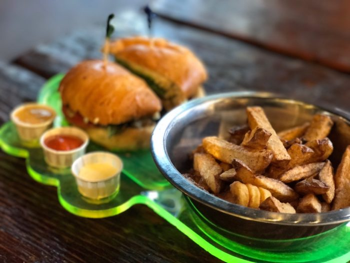 fries and a burger next to dipping sauces