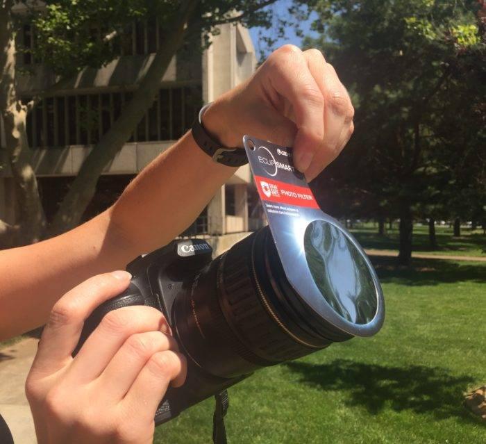 Hand holding digital camera with solar filter
