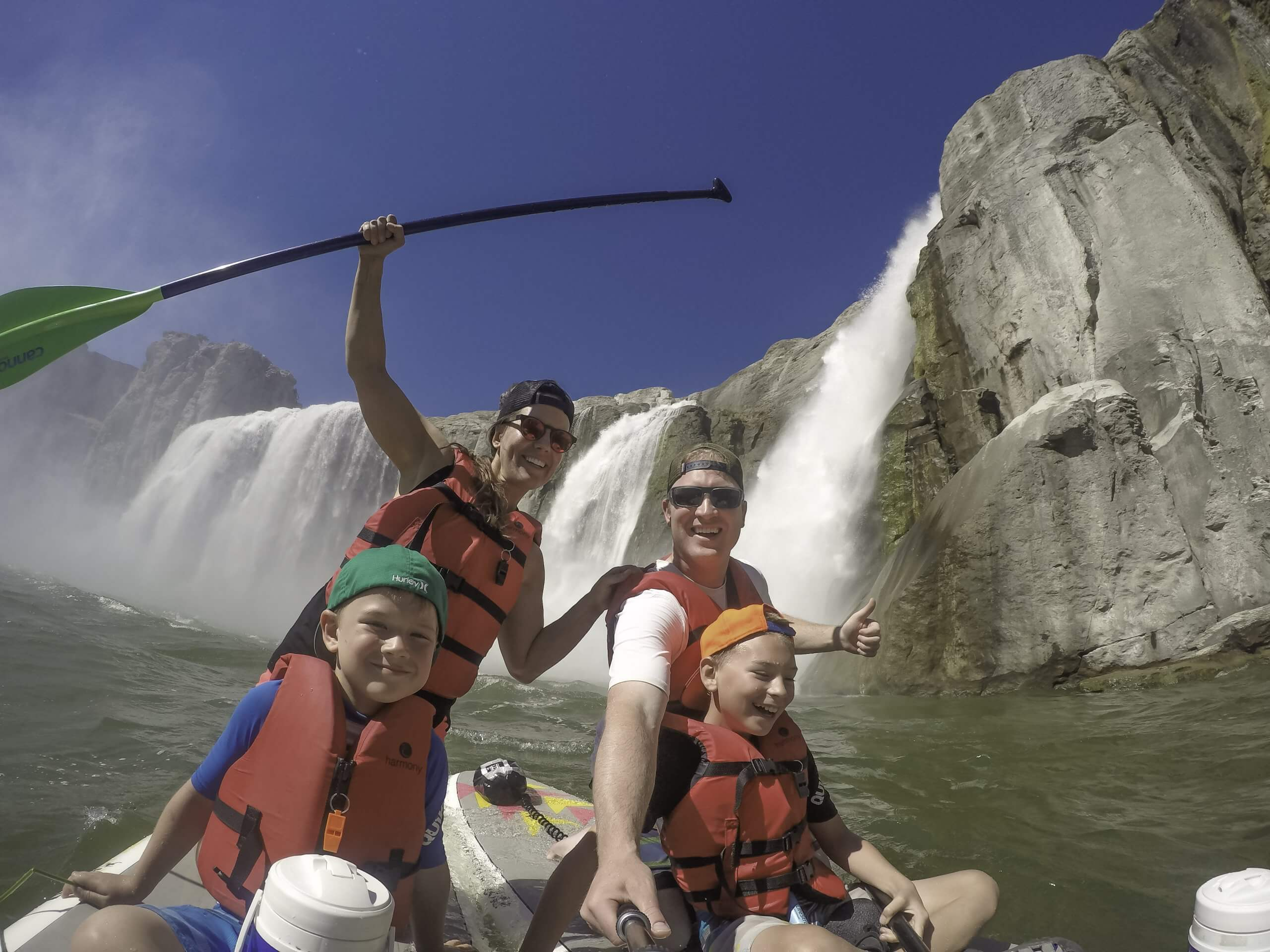 family on paddle board in front of waterfall
