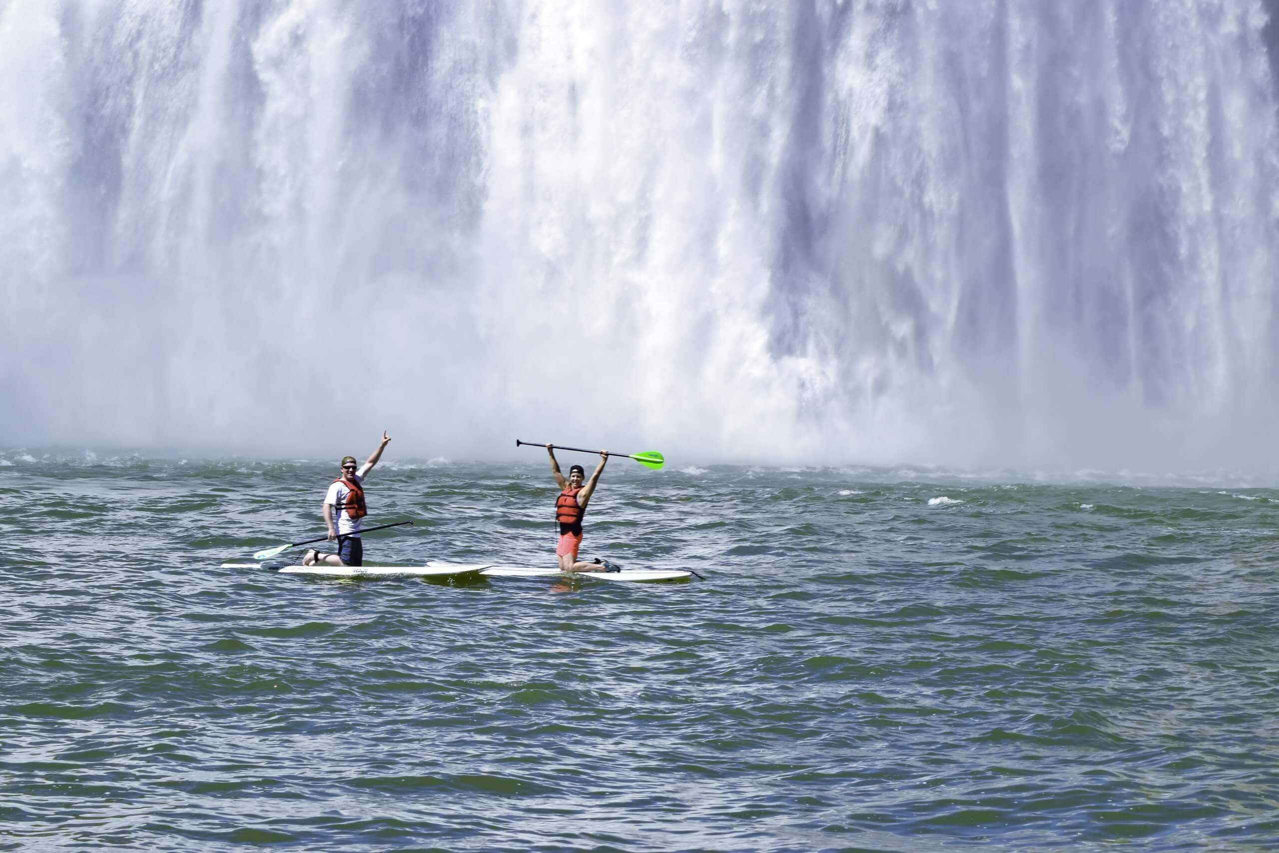 people on paddle board by waterfall