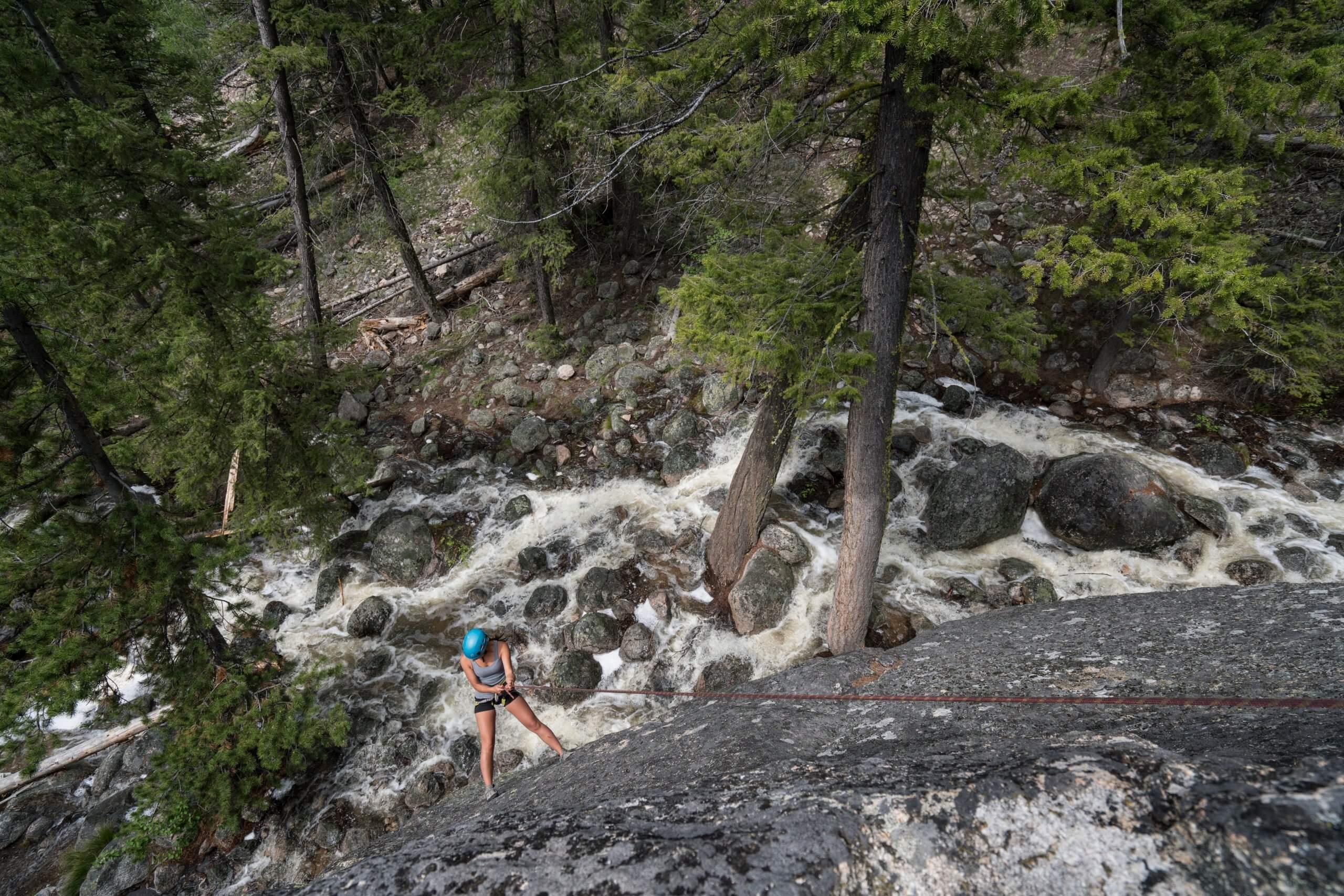 rock climber above a mountain stream
