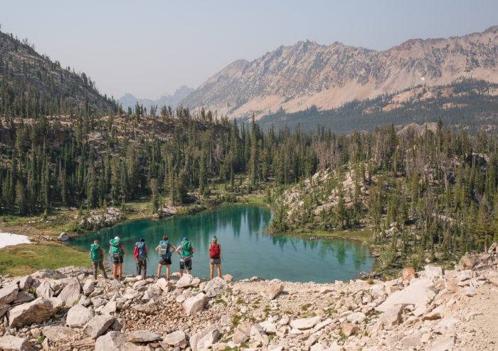 people standing on mountain looking at a lake