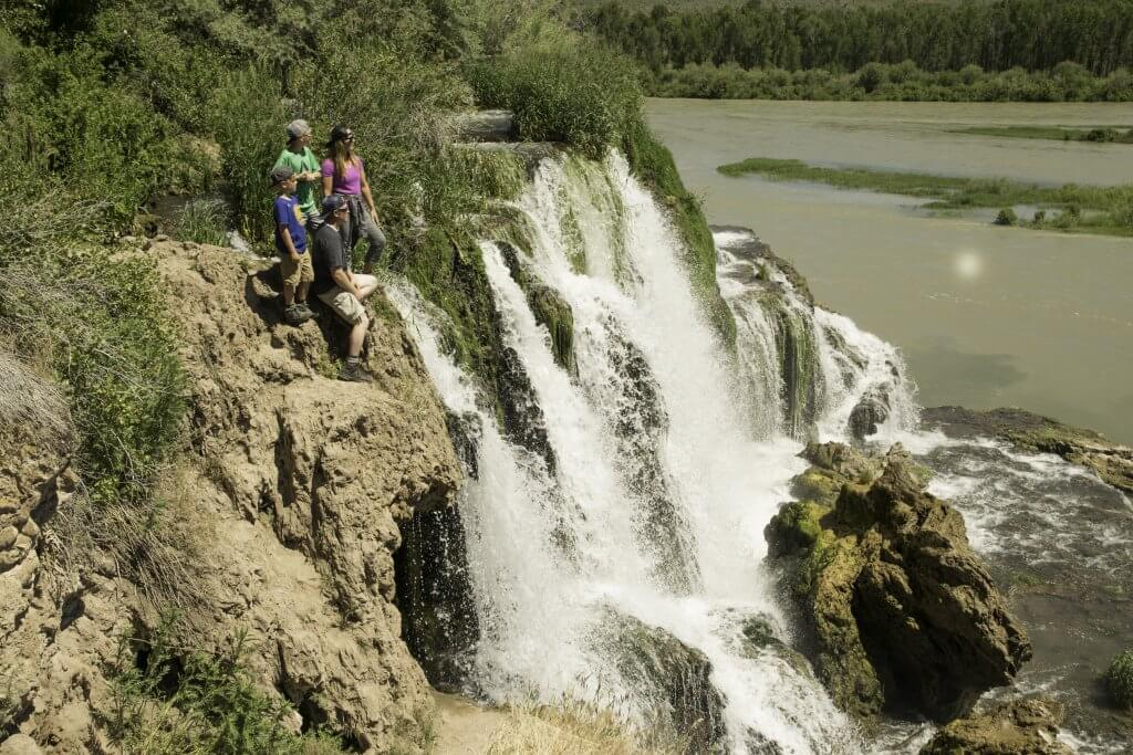 family standing at the top of waterfall