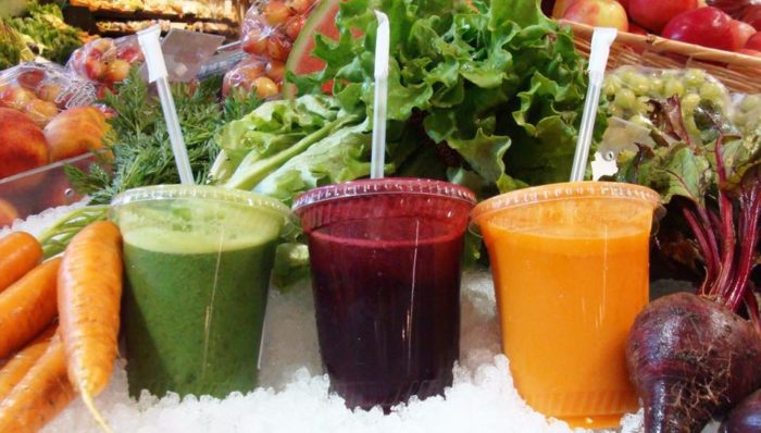 a collection of juices and fresh vegetables
