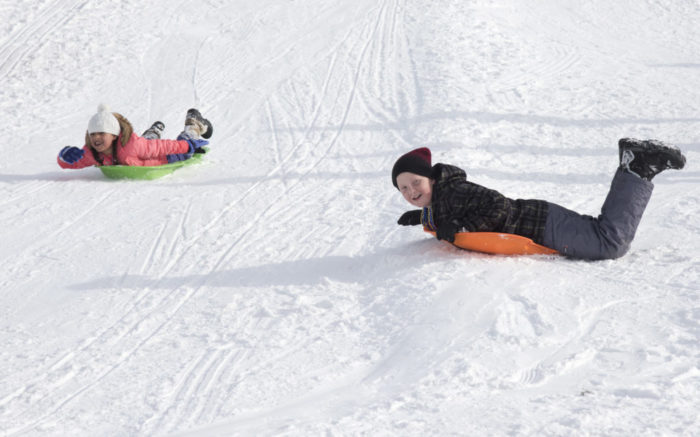 kids on a snow tubing hill