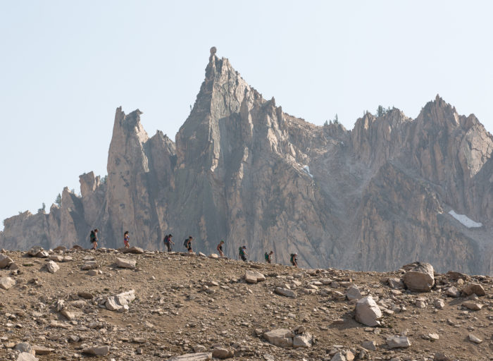 hikers in front of rugged mountains