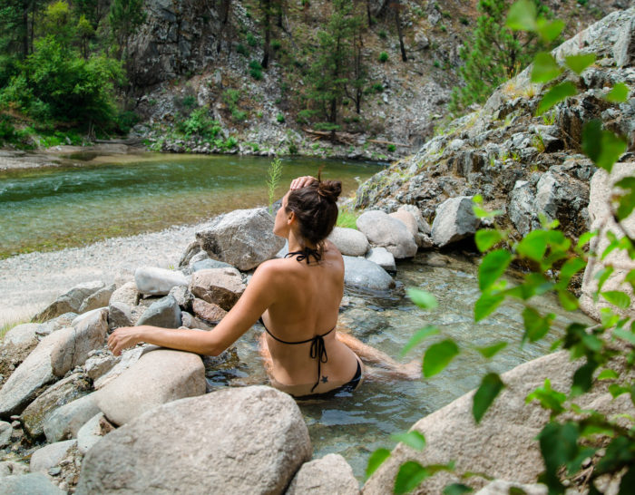 woman sitting in mountain hot spring