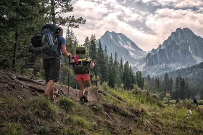 hikers in rugged mountain peaks.