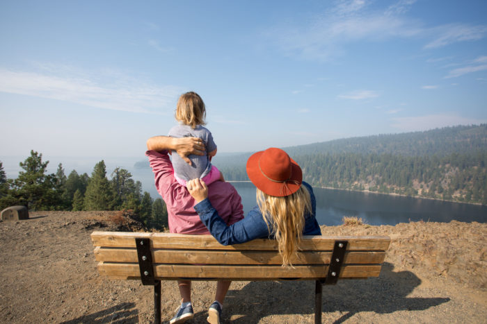 family on bench overlooking lake