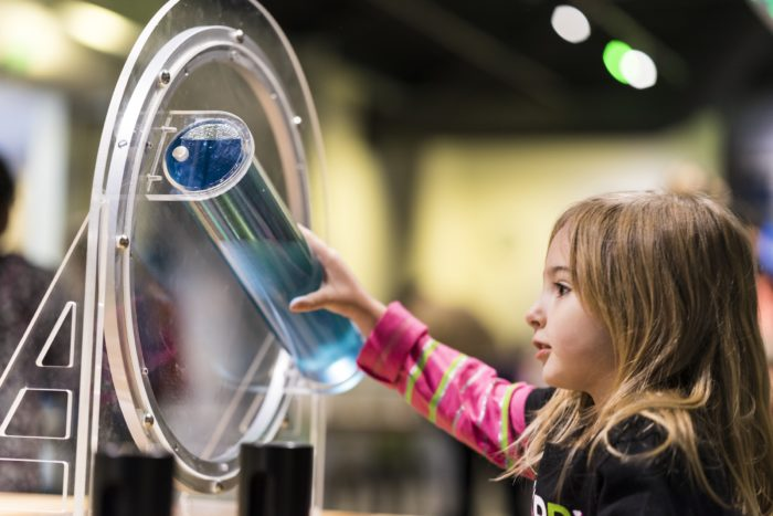little girl playing with science exhibit