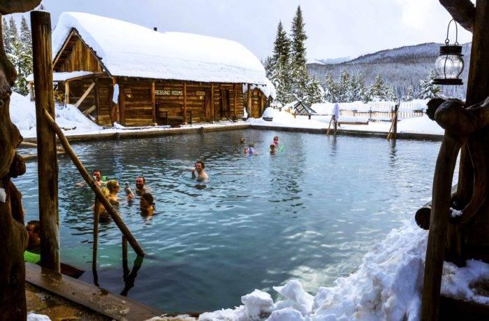 people soaking in rustic hot pool