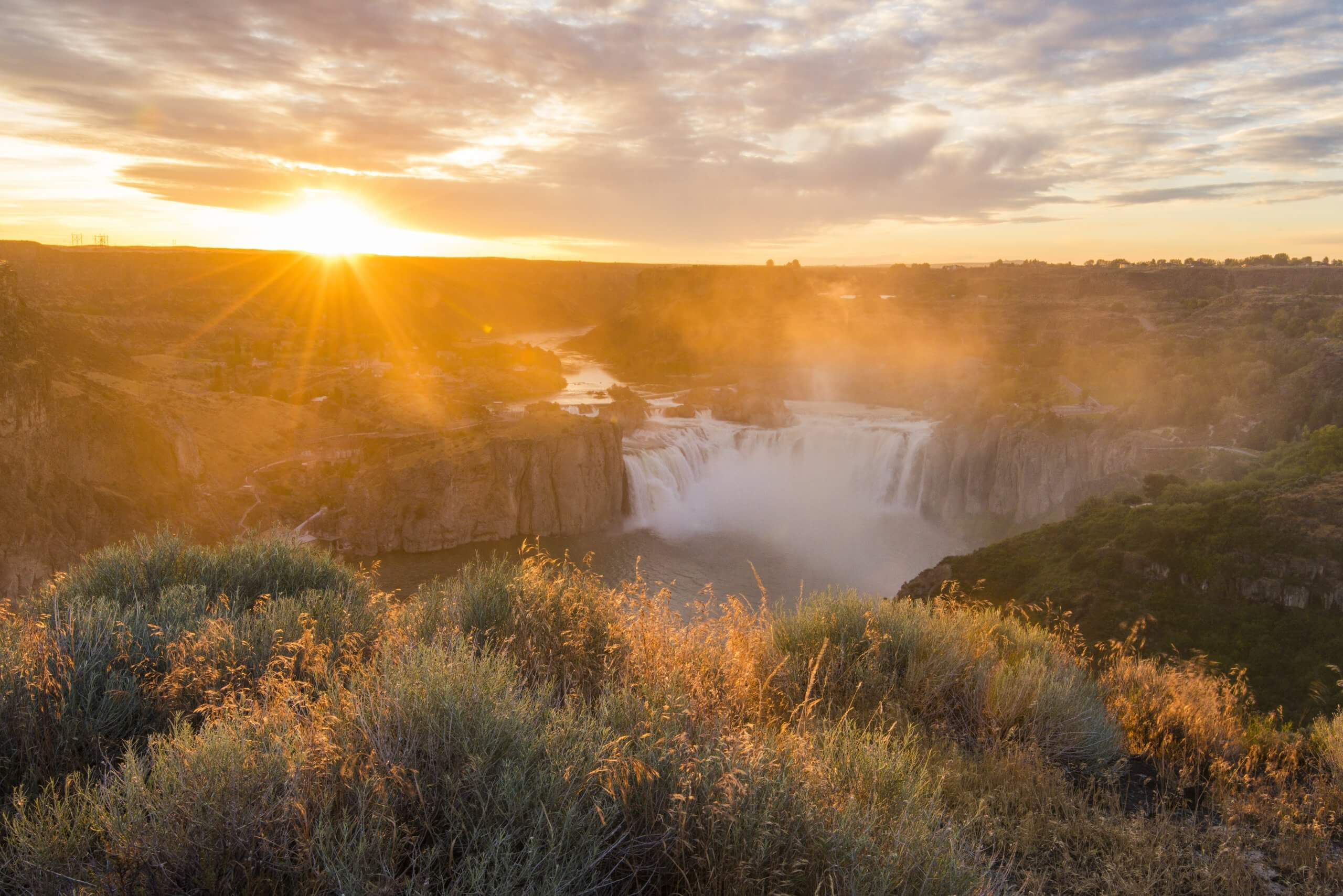A view of Shoshone Falls from the viewing deck in the summer as the sun sets.