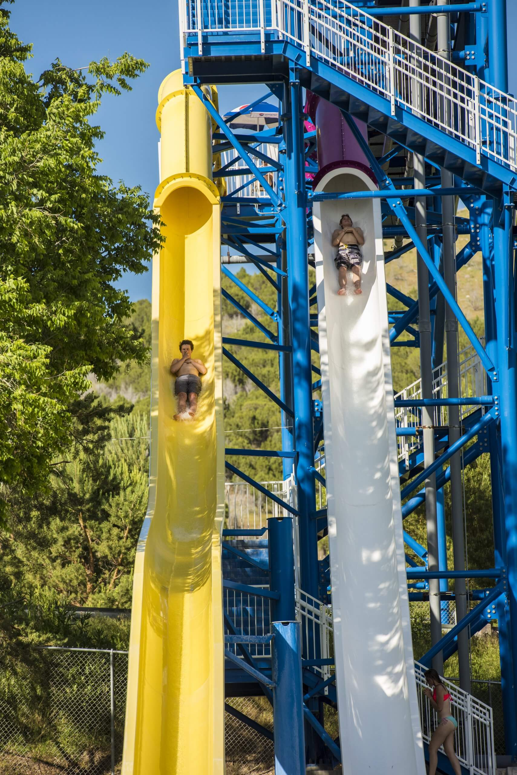 Kids sliding down slides at Lava Hot Springs Olympic Swimming Pool & Waterpark.