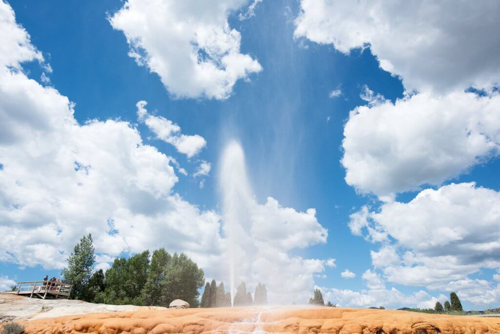 Soda Springs Geyser erupting against a blue sky with trees in the background