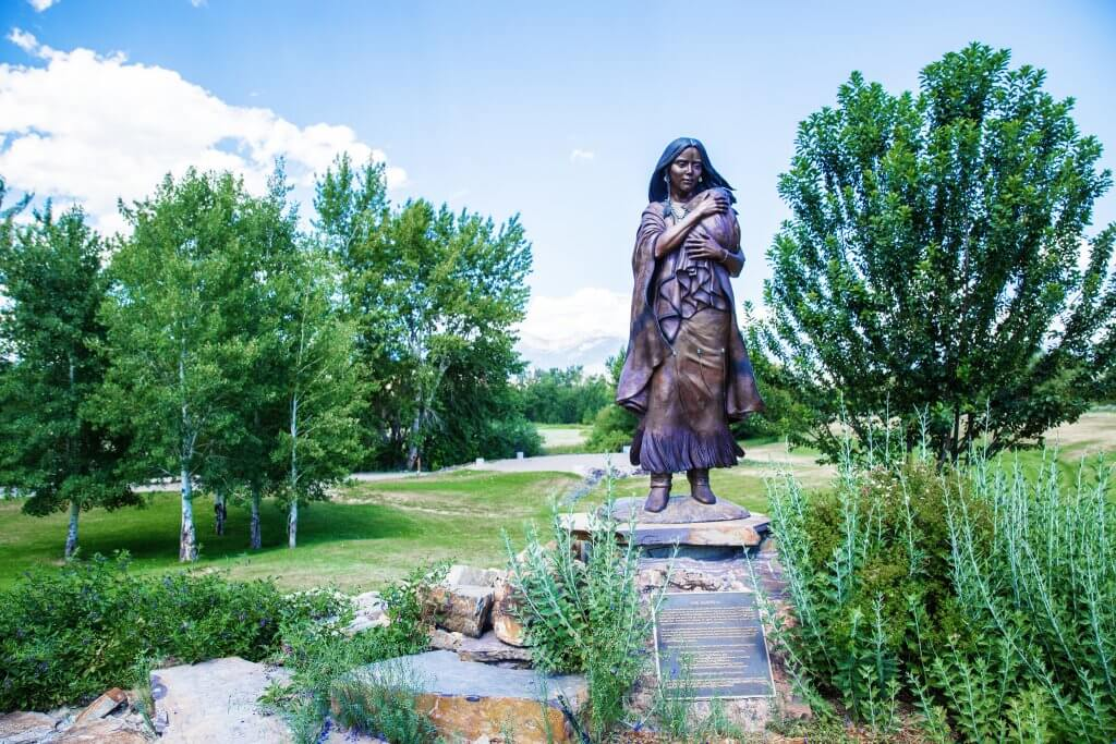 a bronze statue of Sacajawea in a park surrounded by trees