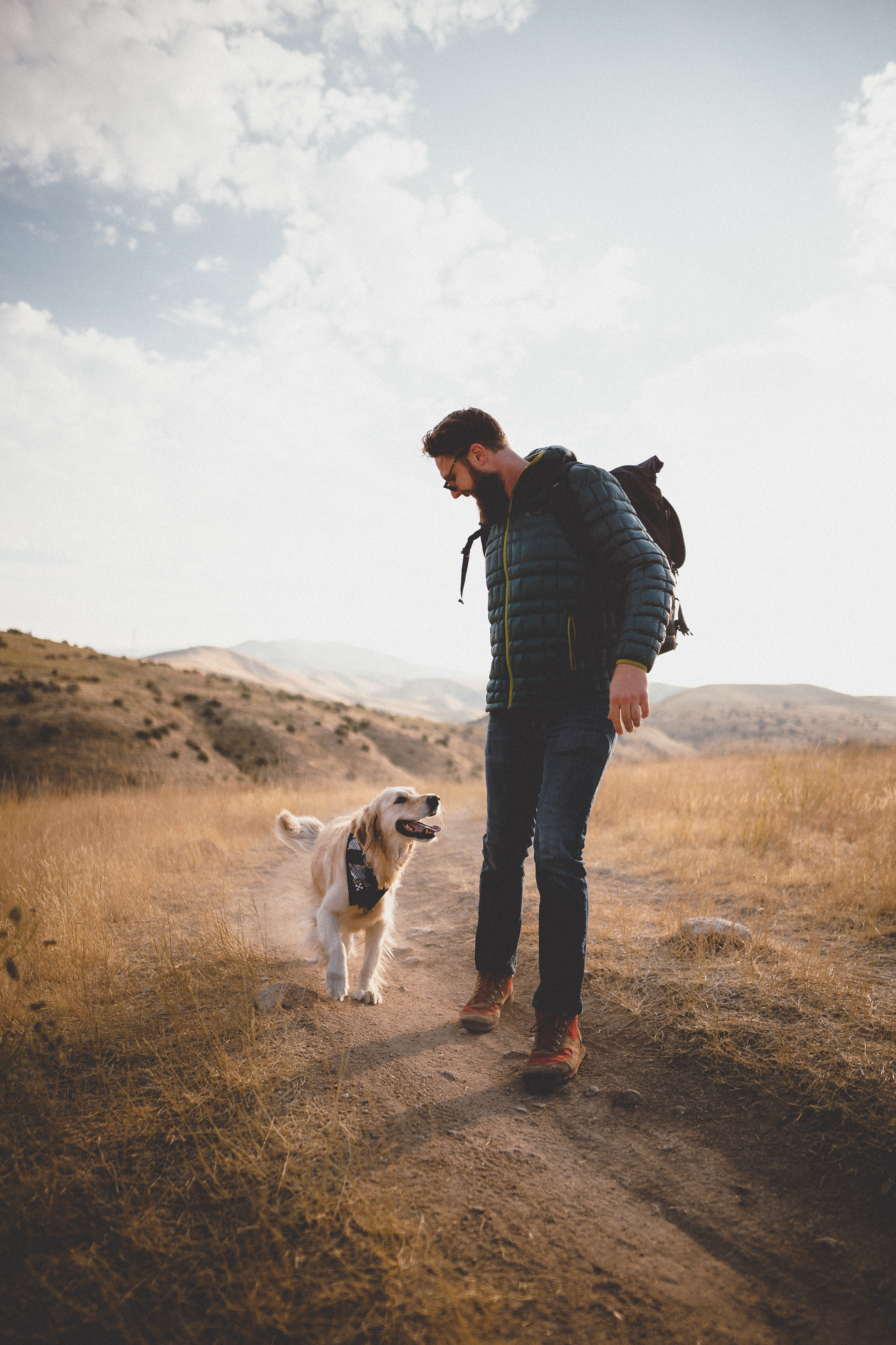 man and dog walking on trail.