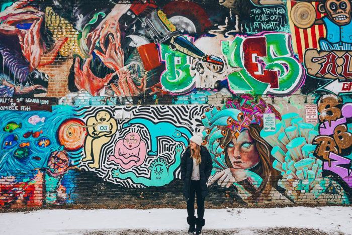 woman in front of graffiti wall