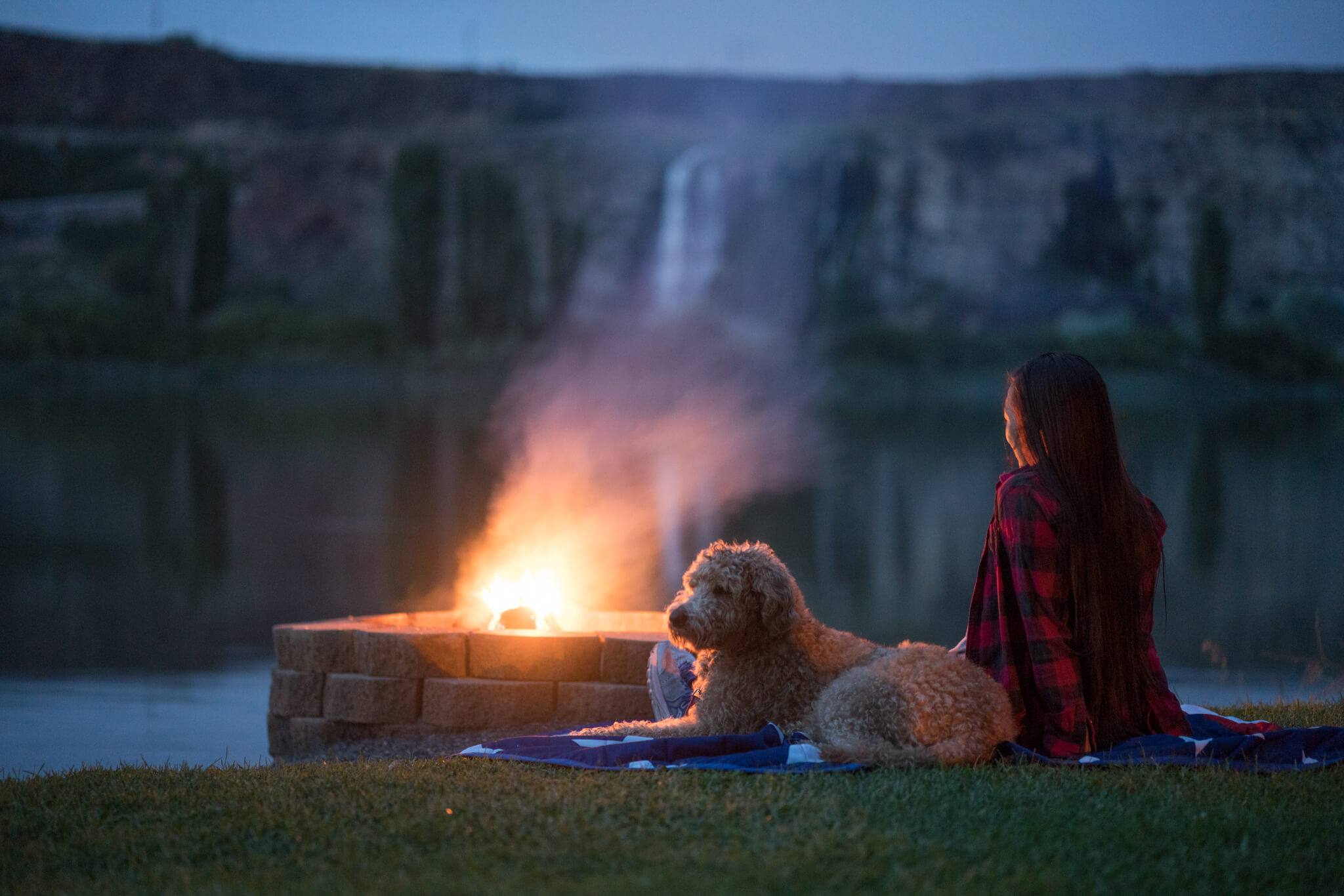 woman and dog next to campfire