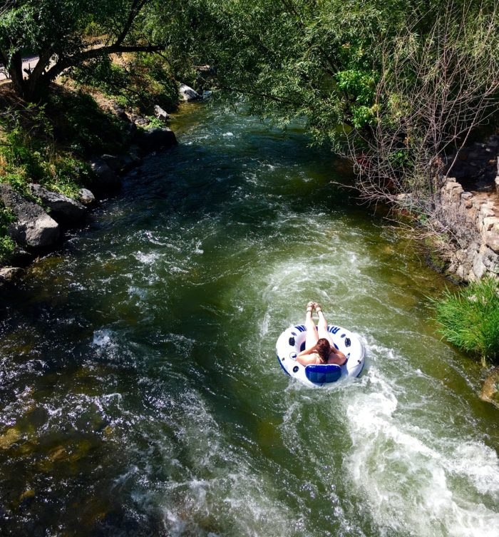 person floating a river in an inner tube