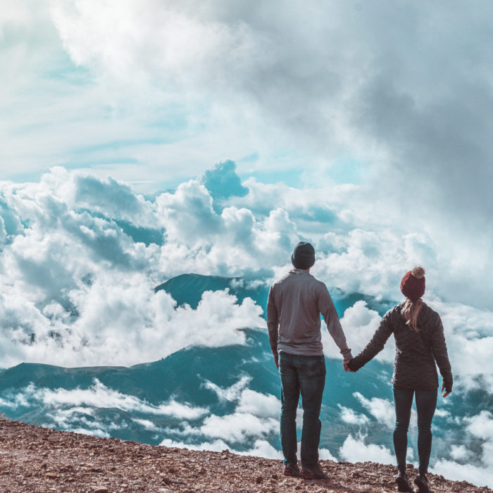 two people standing on a hilltop