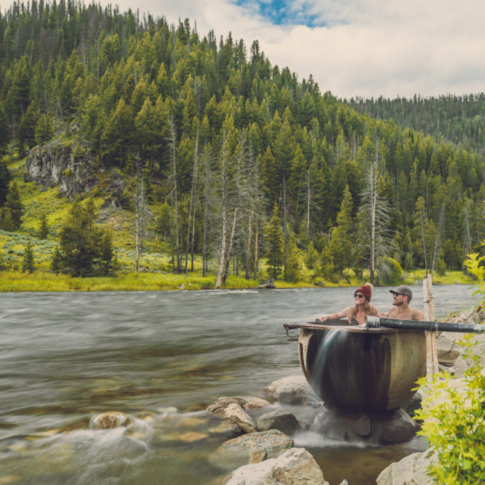 people sitting in a riverside hot tub
