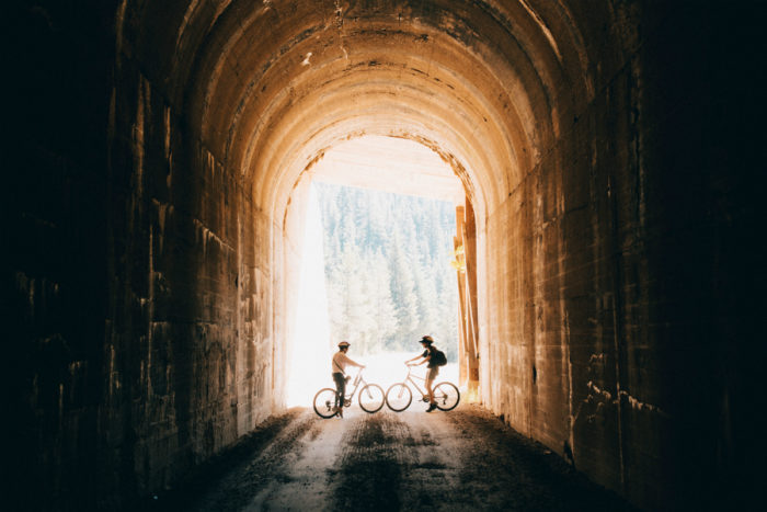 two bike riders in a tunnel