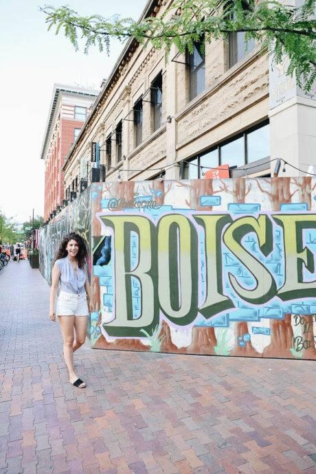 woman standing next a mural