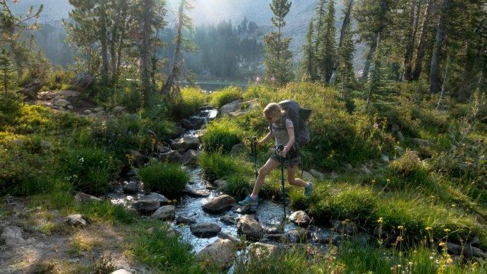 hiker crossing a stream