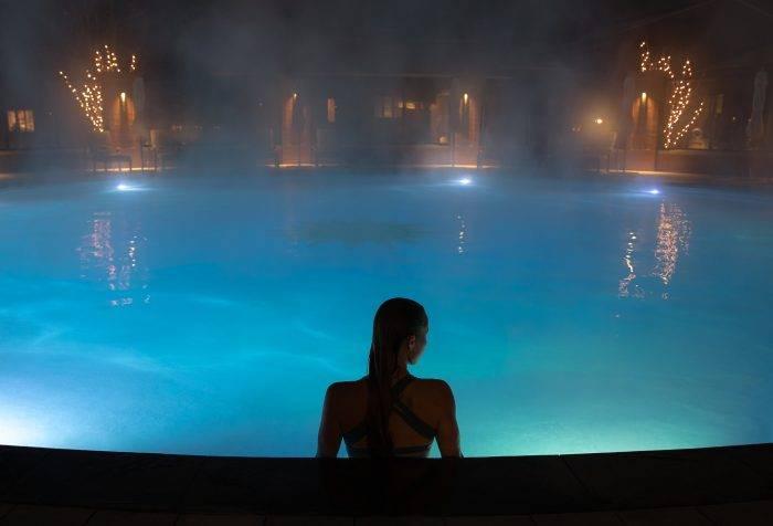 woman sitting in pool at night