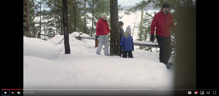 A family snowshoeing near a snow-covered lake in Idaho.