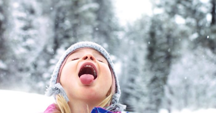 A little girl catching a snowflake on her tongue.