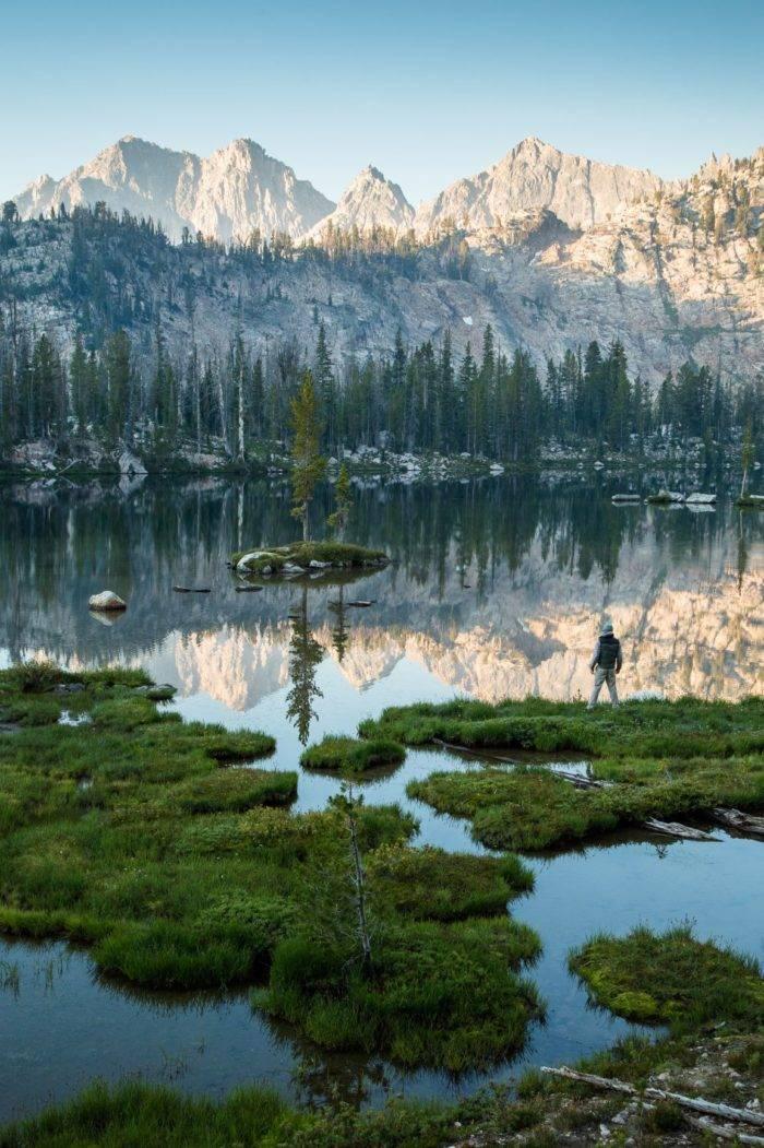 A man standing near a mountain lake