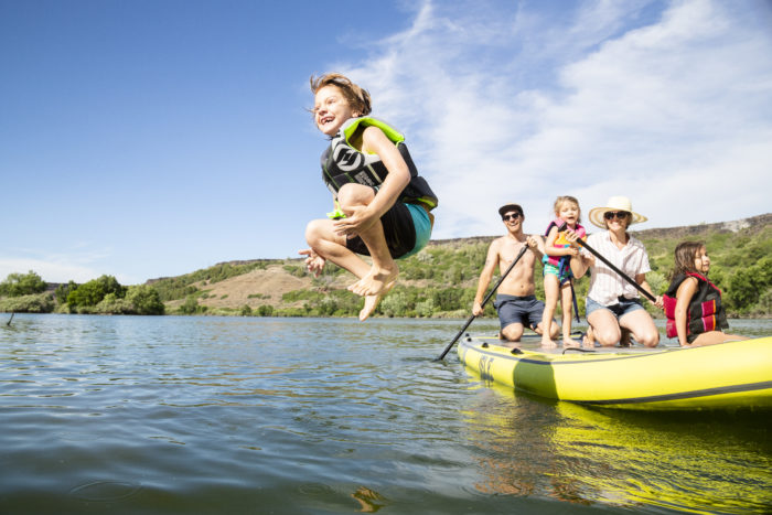 A child jumping off the paddle board into the Snake River to swim.