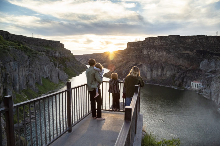 A family on the viewing deck watching the sunset at Shoshone Falls.